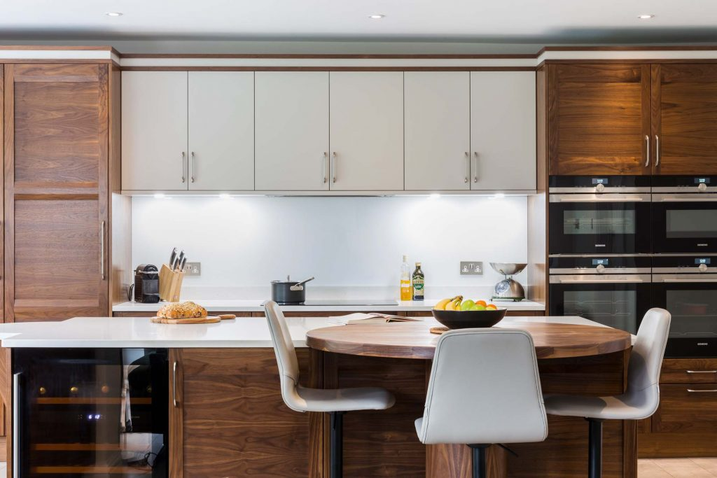 Strata Kitchen straight on view with wooden island and white bar stools