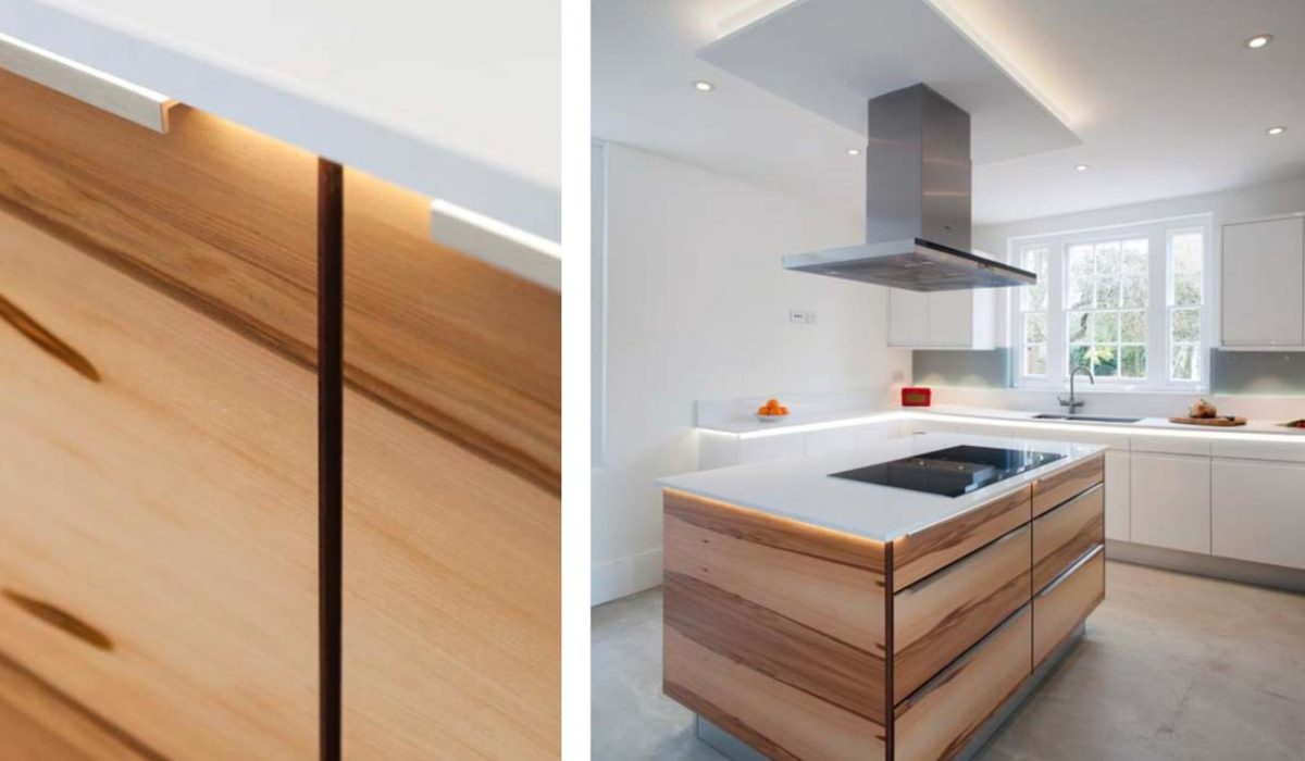 Gloss contemporary kitchen with close up of sleek drawer handles and walnut island