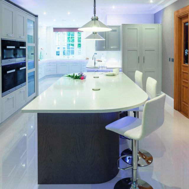 Traditional kitchen in light grey with curved cabinets and island