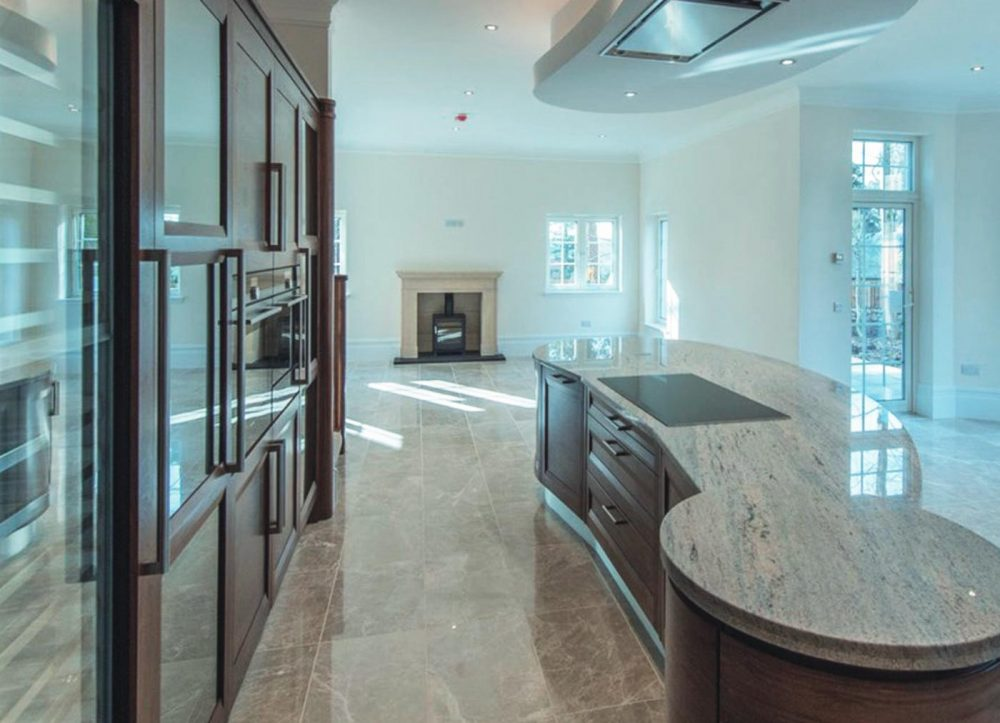 Large open-plan timber kitchen with marble floor and curved island