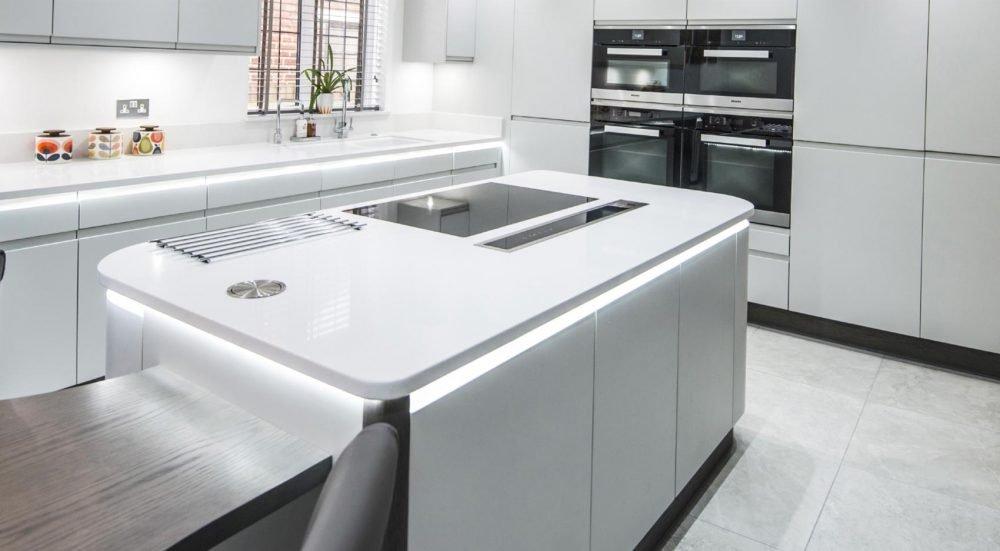 White modern handleless kitchen rectangular island with curved corner