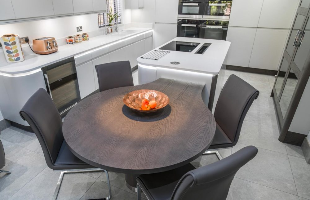 White modern handleless kitchen with round wooden table