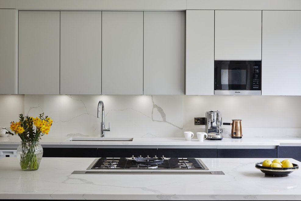 Off-white handleless kitchen with hob on island and daffodils