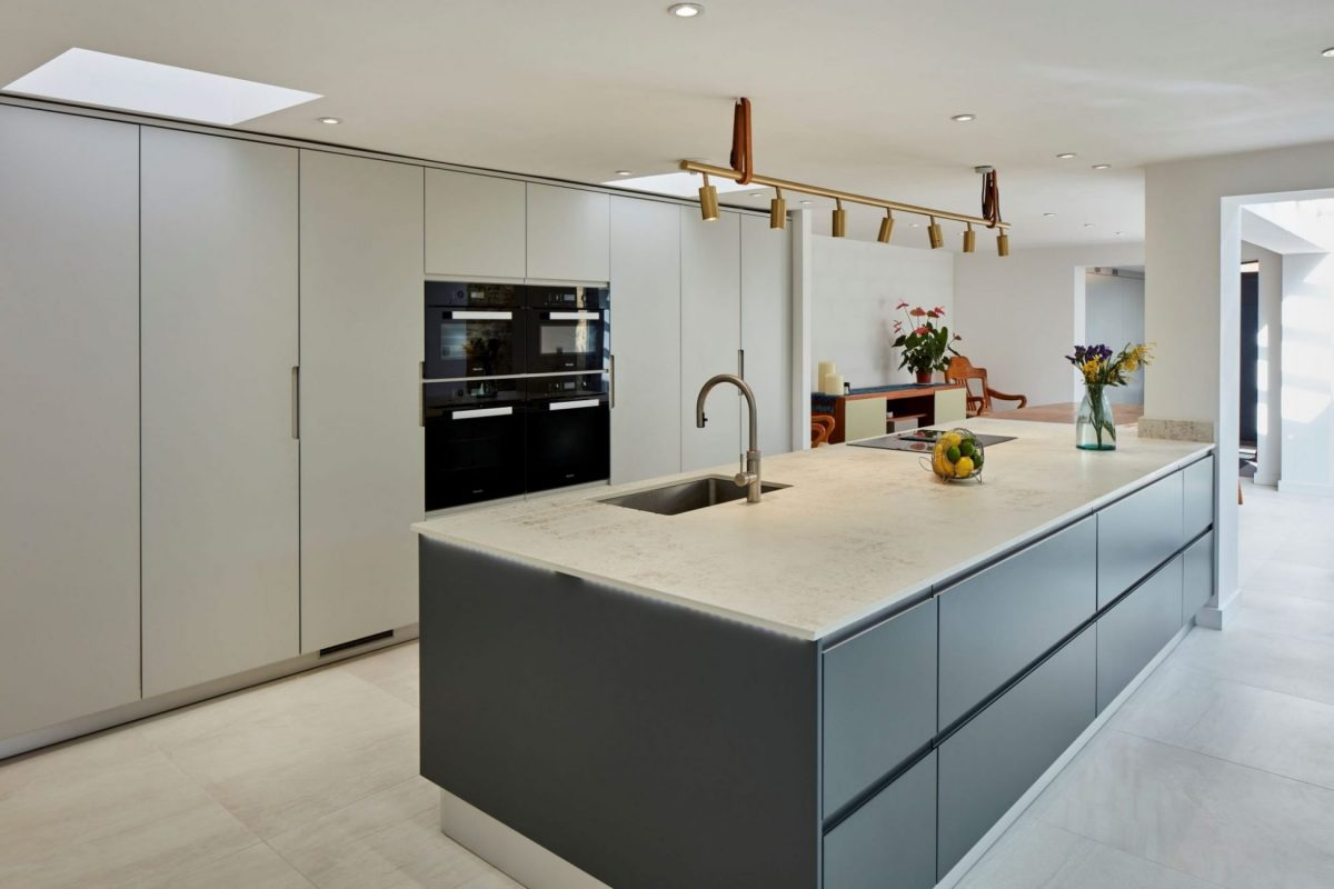 open plan kitchen with large dark grey kitchen island and light grey floor to ceiling cabinets