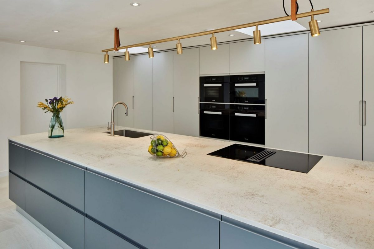 large dark grey kitchen island with integrated hob and tap with handing brass light overhead