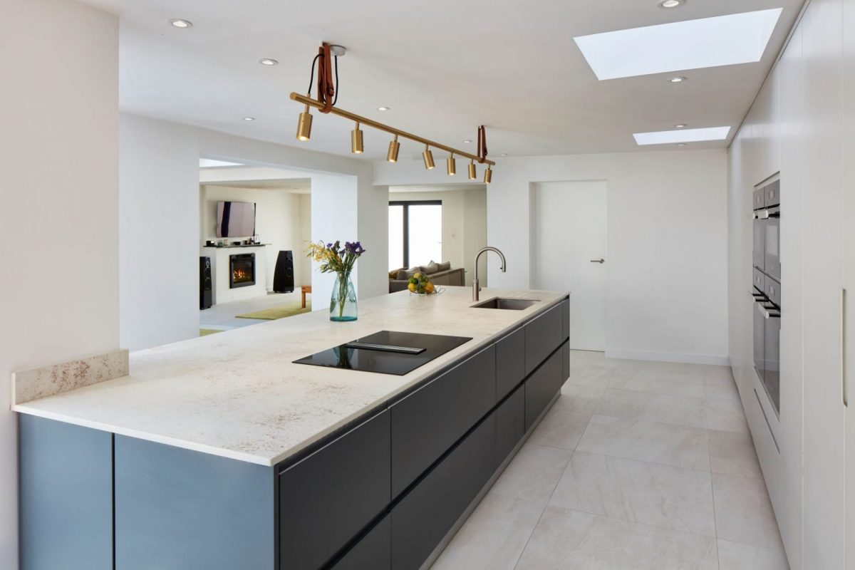 Large dark grey kitchen island with off-white textured worktop and hanging brass lights