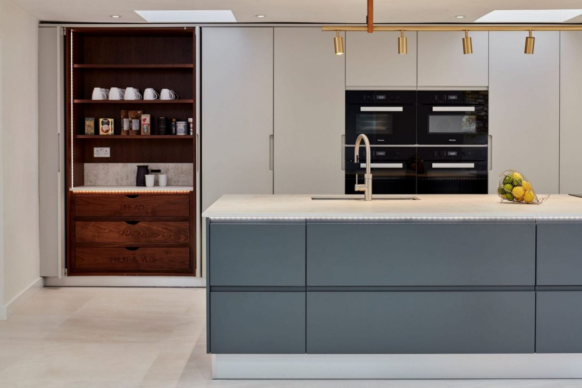 opened wooden pantry cupboard in kitchen with dark grey kitchen island