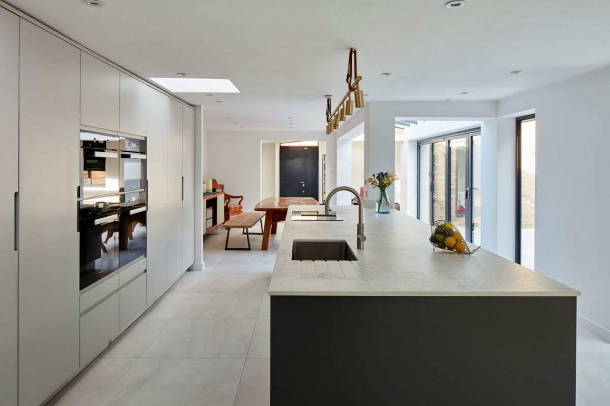 handleless kitchen with light grey floor to ceiling cabinets and large dark grey kitchen island
