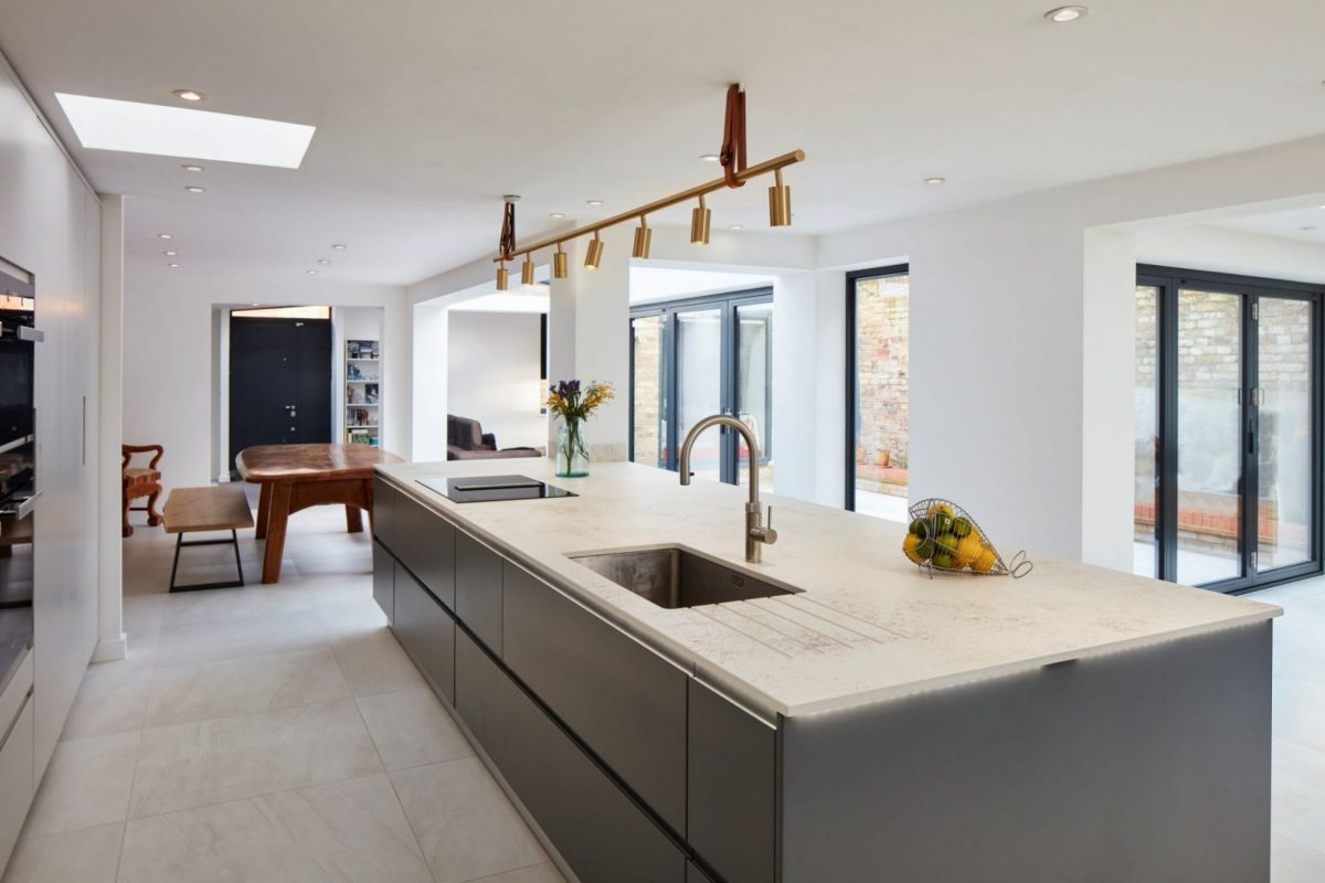 large grey kitchen island with brass hanging light feature