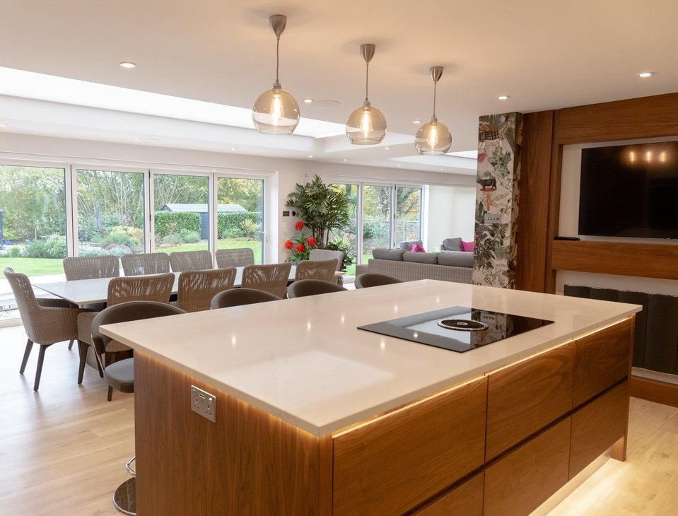 Wooden kitchen island with pendant glass lights and view onto garden