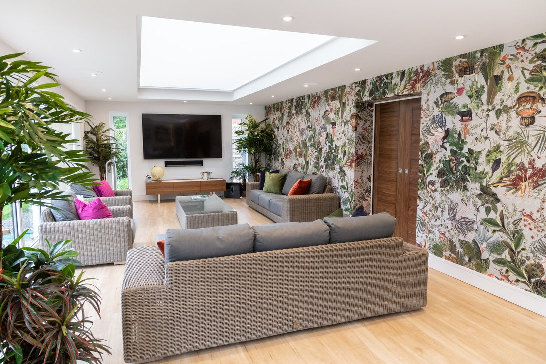 Dining area with plant themed wallpaper and skylight with TV