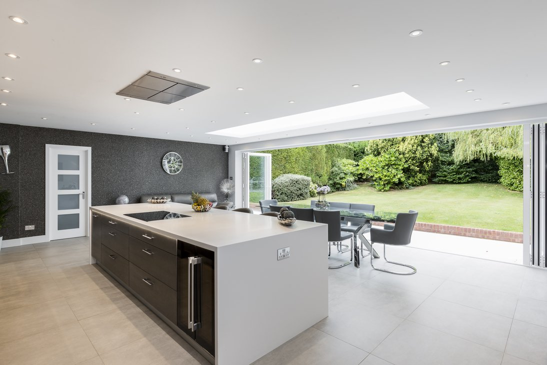 white and grey kitchen island with glass dining table and bi-fold doors open onto landscaped garden