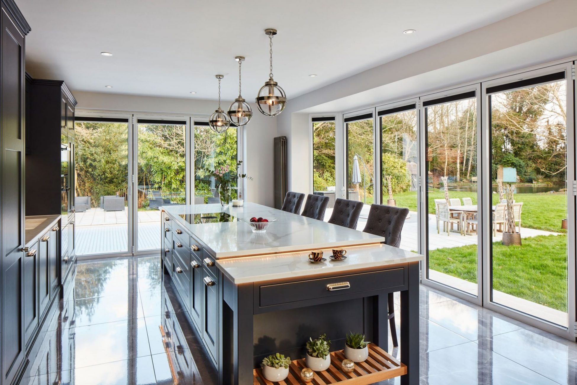 Dark blue kitchen island with silver globe pendant lights view glass doors across two walls