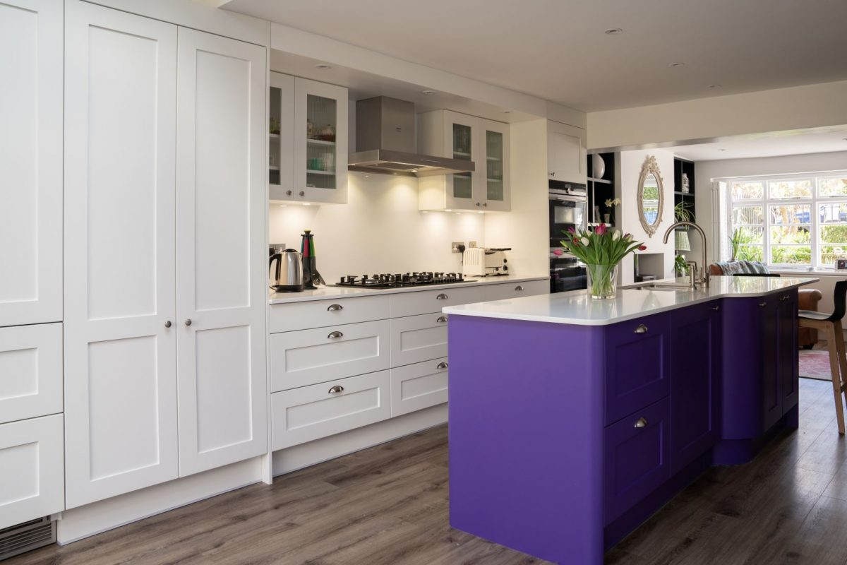 White shaker kitchen with bright purple kitchen island