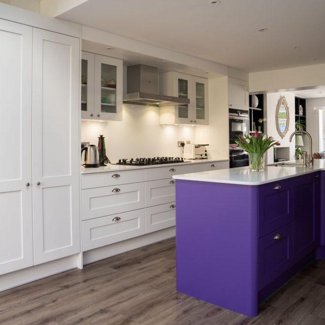 White shaker kitchen with bright purple kitchen island