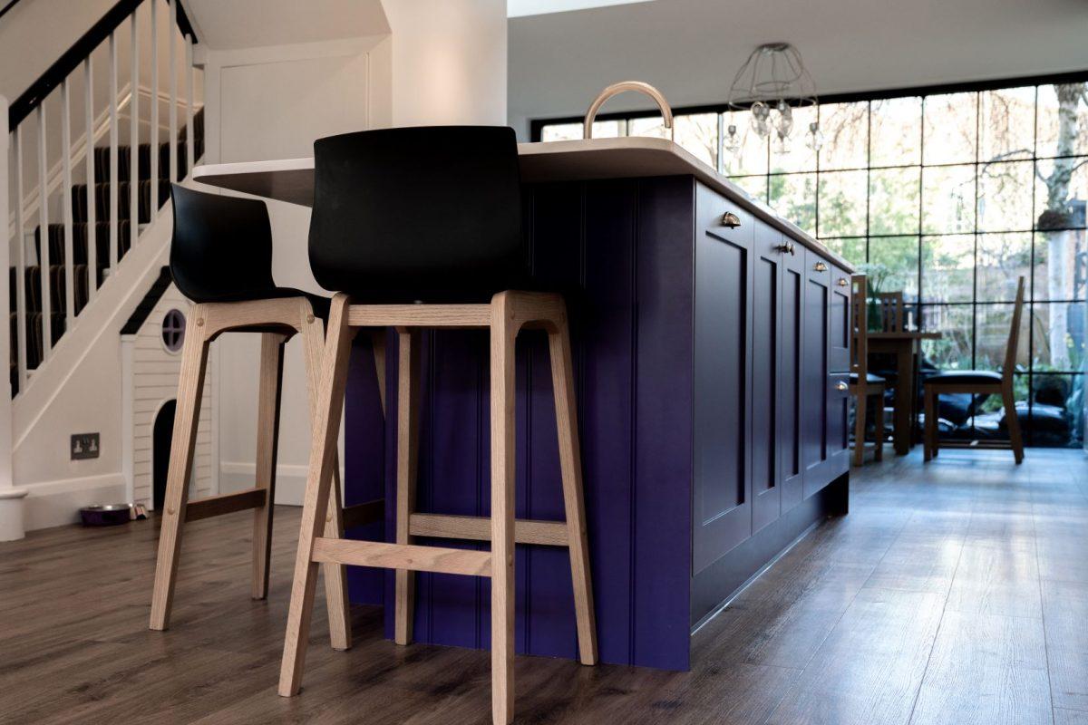 Purple kitchen island with wooden stools
