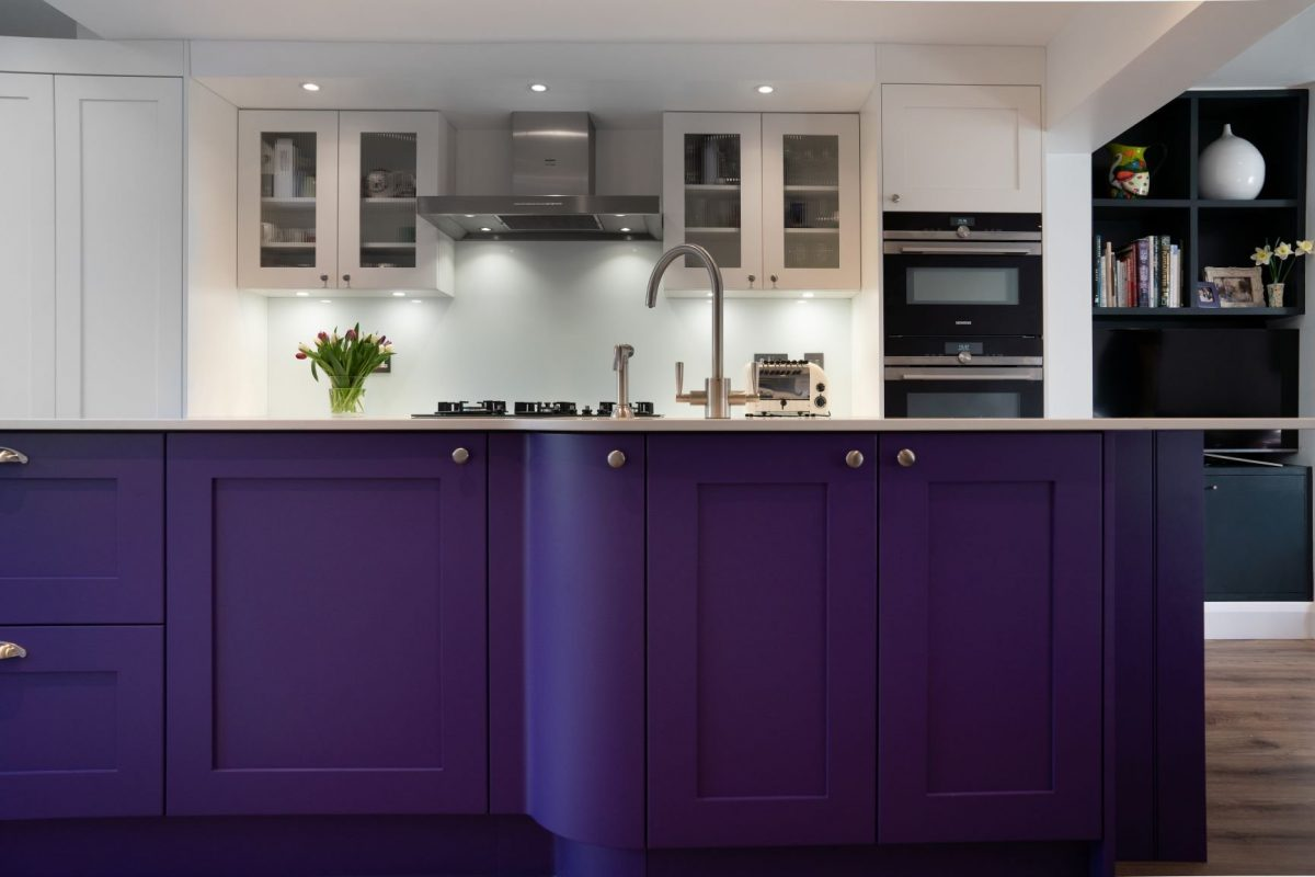 Bright purple curved kitchen island with small chrome circular handles and chrome tap