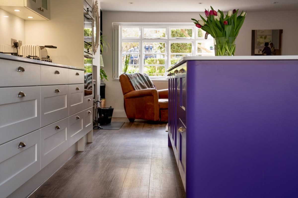 Purple kitchen island with white kitchen drawers