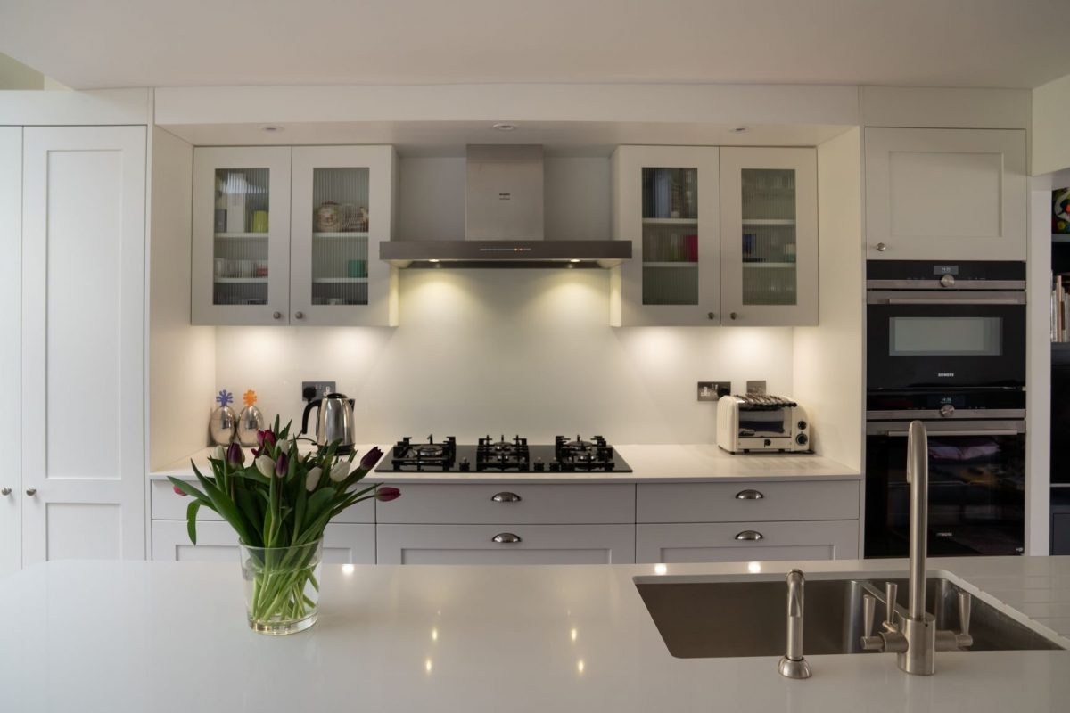White shaker kitchen with white worktop and chrome sink and tap
