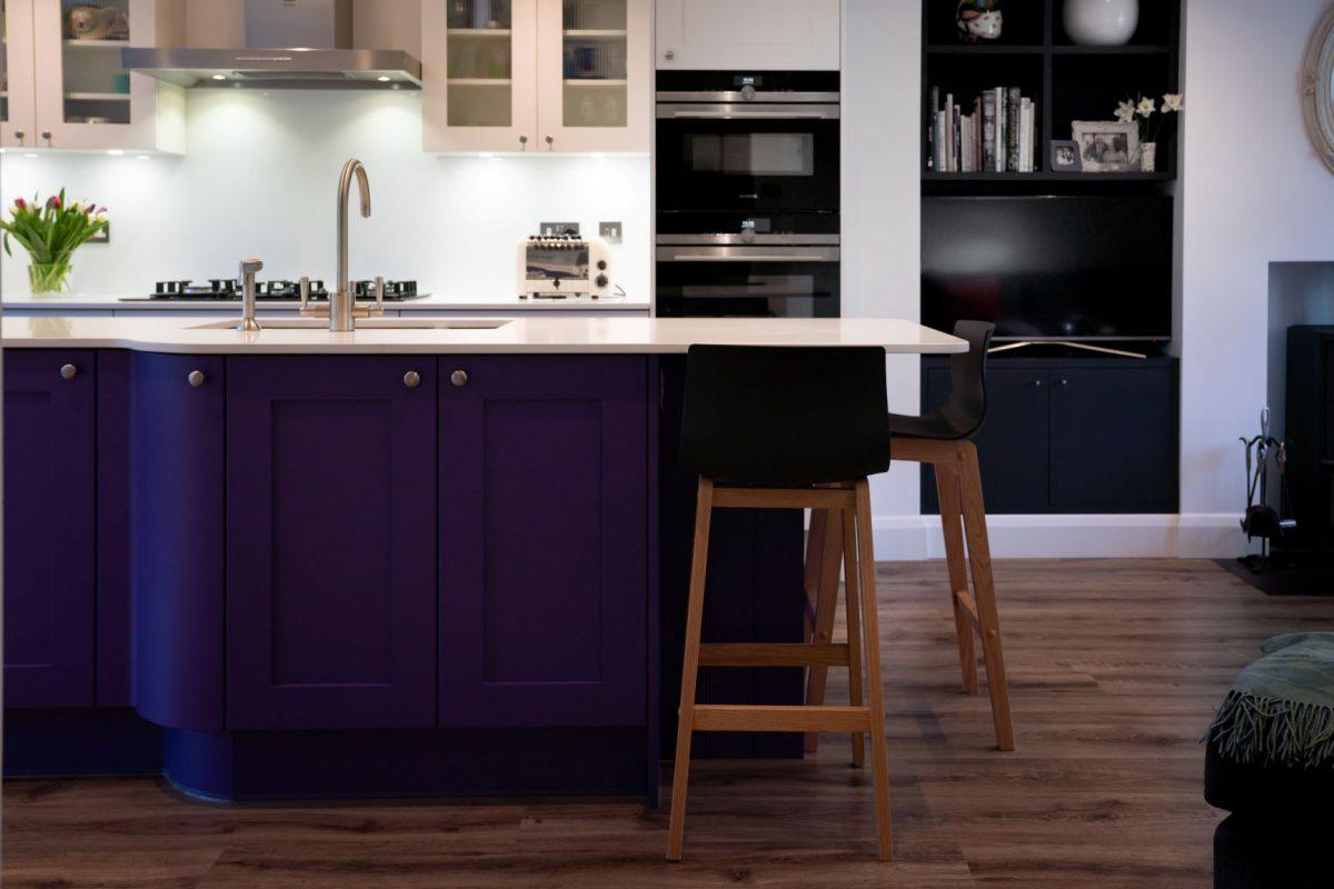 Curved purple kitchen island with white wortop
