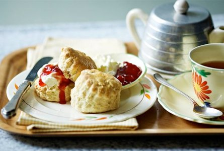 Scones with jam and cream served with tea on wooden tray