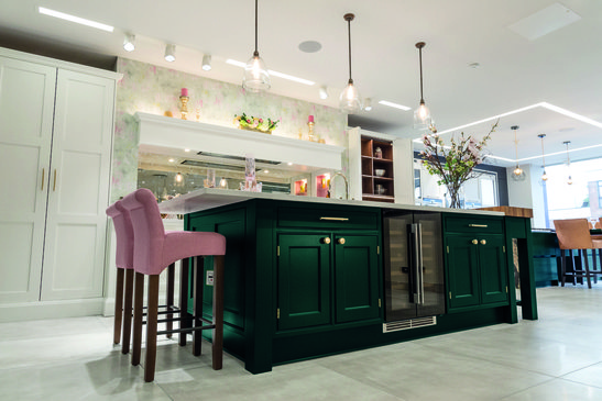Green kitchen island with pink stools