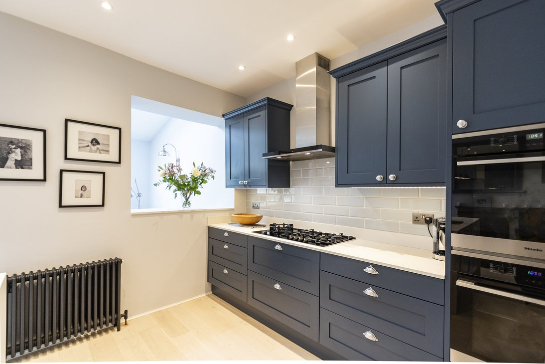 Blue shaker kitchen with dark grey iron radiator
