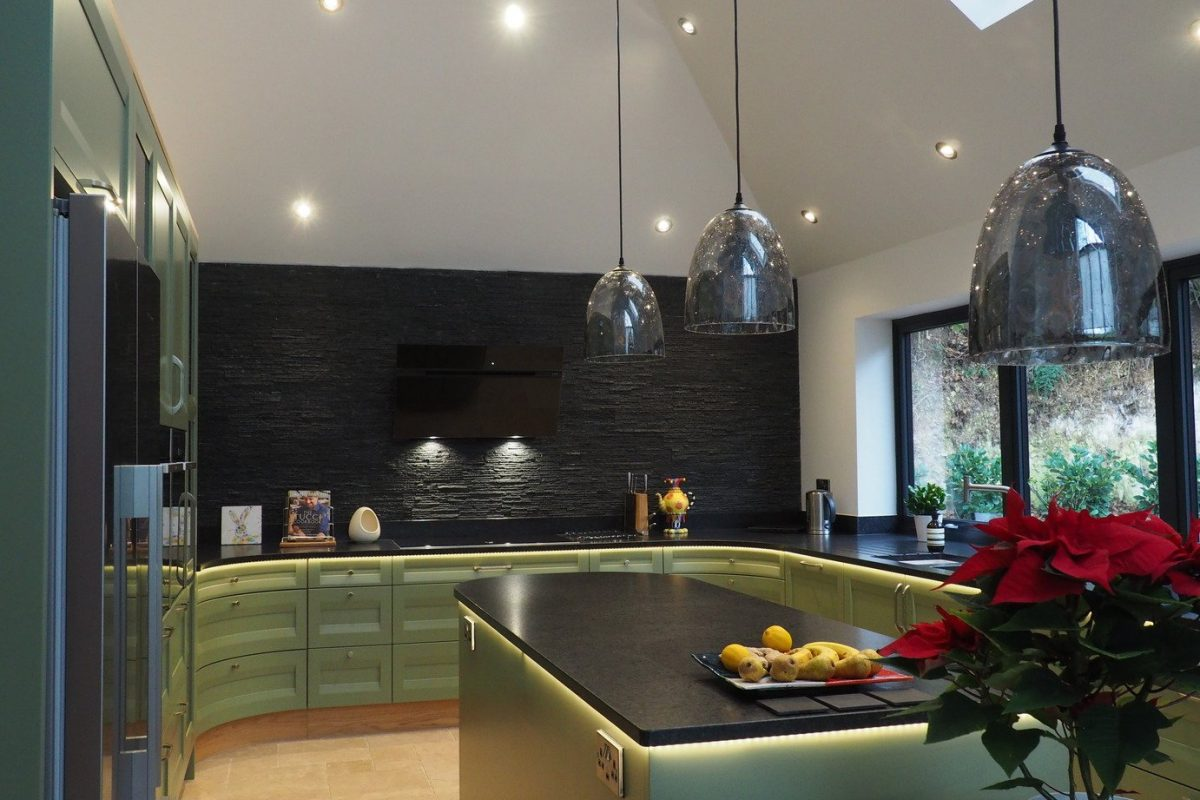 Sage green kitchen with black feature wall