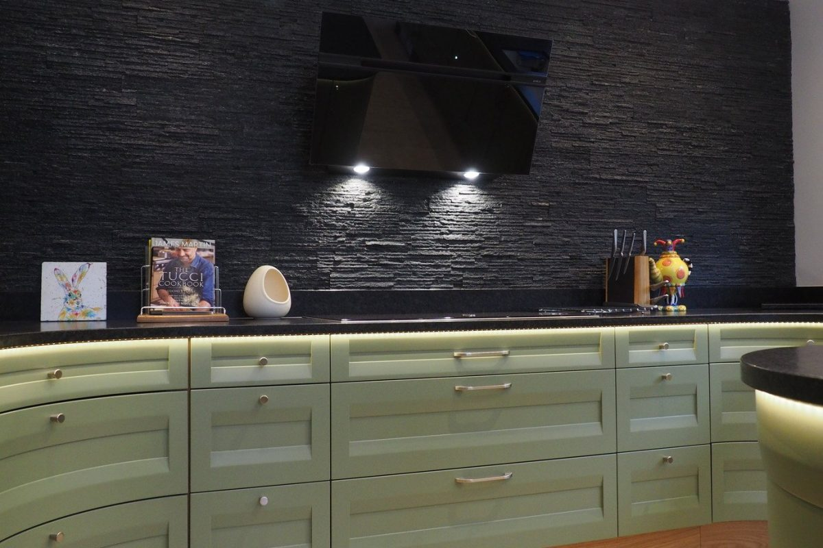 sage green kitchen cupboard and black splitface wall with TV screen