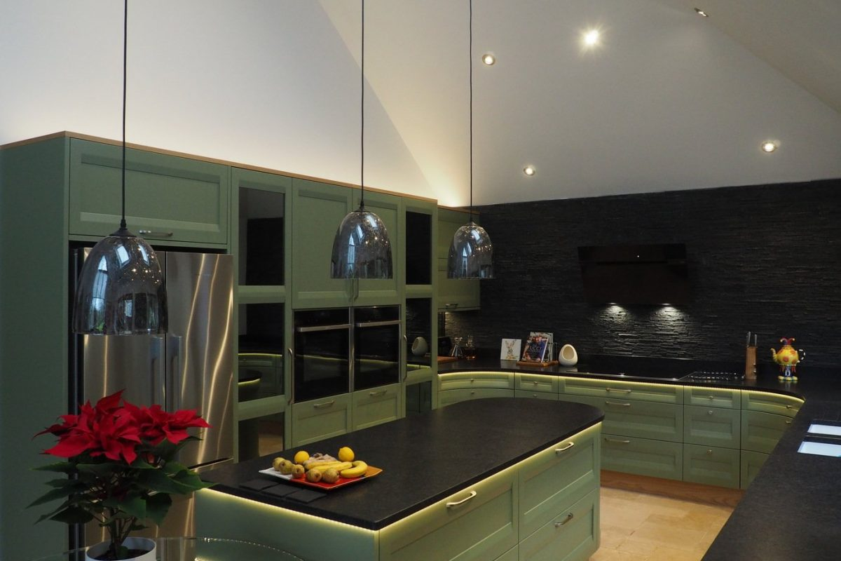 Sage green kitchen with pendant lighting over curved kitchen island