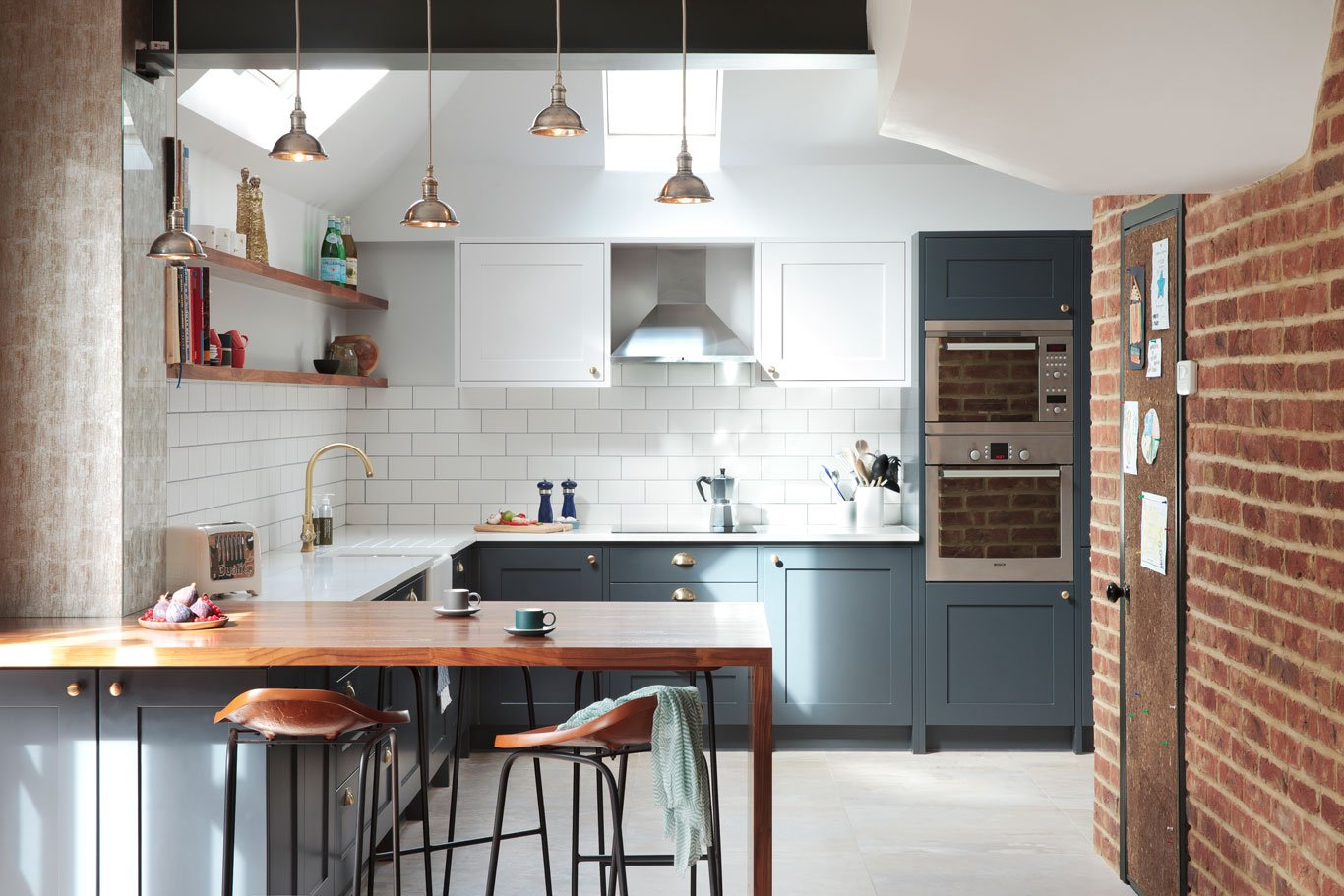 Industrial style kitchen in deep blue with exposed side wall, wooden breakfast bar and pendant lighting
