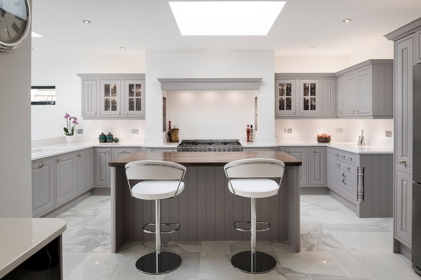 Grey u shaped shaker kitchen with kitchen island, two stalls and wooden work surface