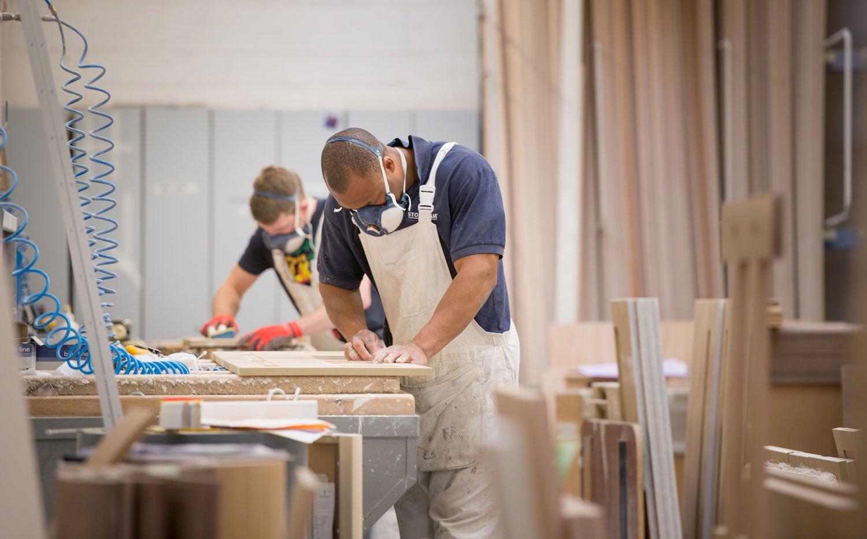Two men hand crafting wood for British kitchens manufacturer Stoneham