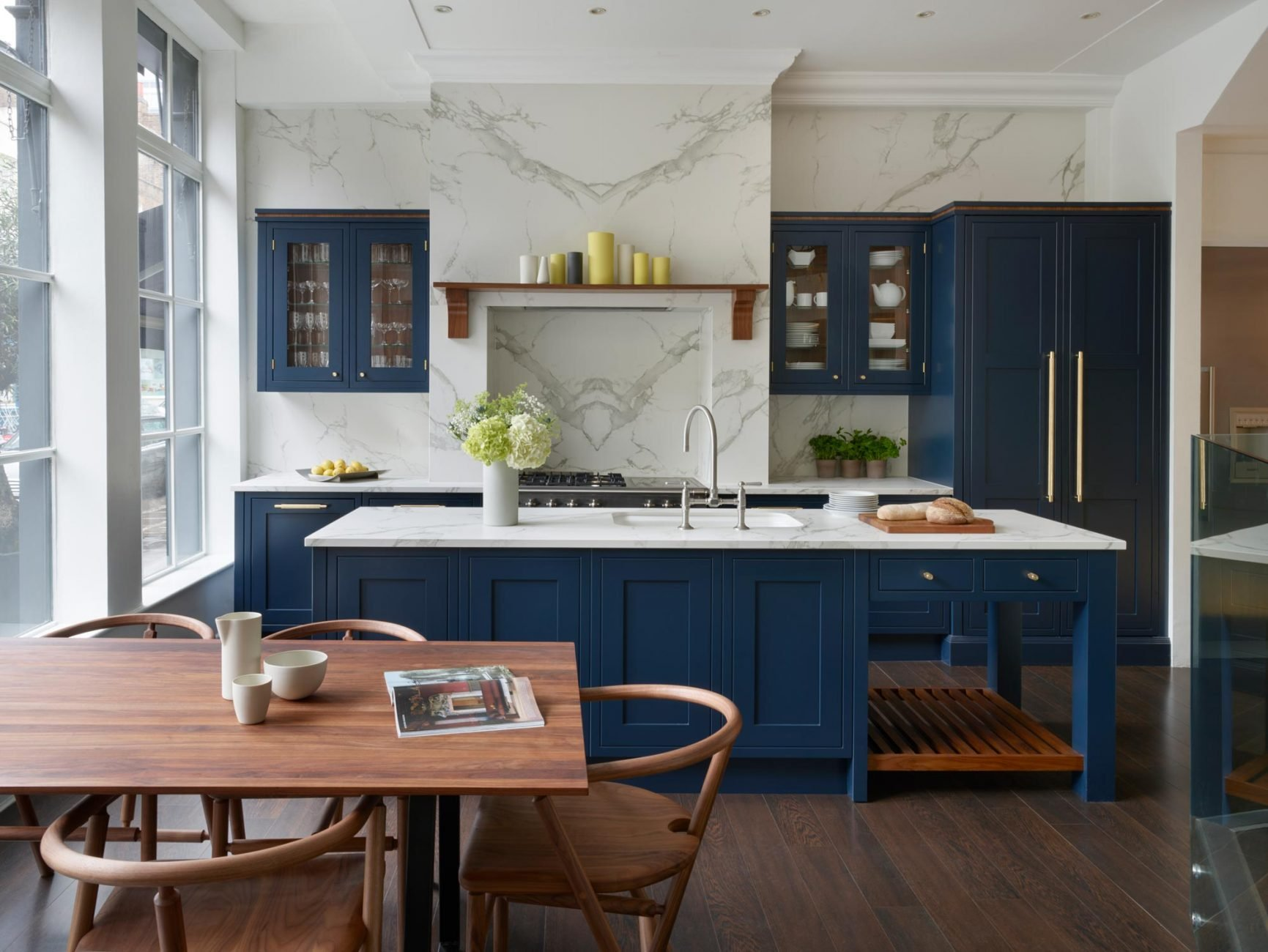 Dark blue kitchen units with quartz worktop and wooden dining table in foreground
