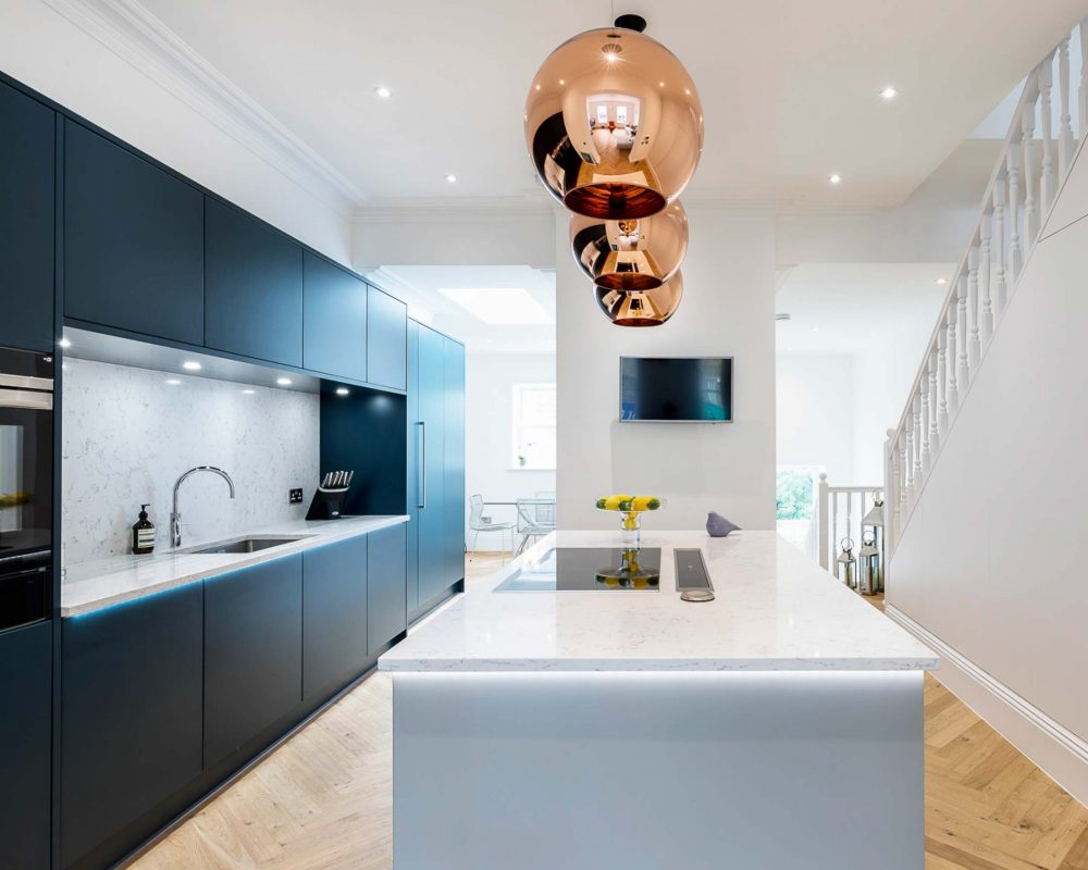 Spacious kitchen with dark blue units flush to wall and soft grey kitchen island with copper pendant lighting features.
