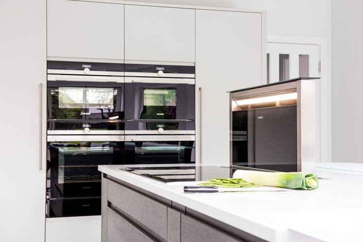White kitchen with induction hob and integrated extractor on the kitchen island