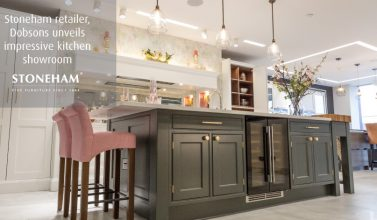 dark grey kitchen island with dusty pink stalls and glass pendant lighting