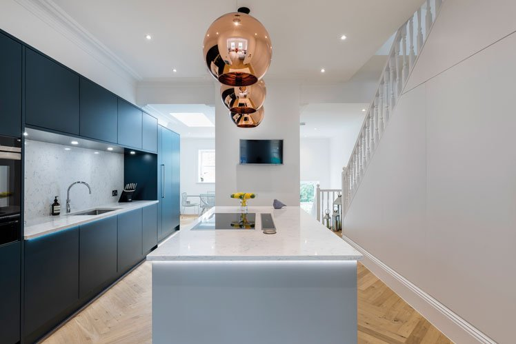 Blue kitchen cupboards with copper pendant lighting hanging over kitchen island