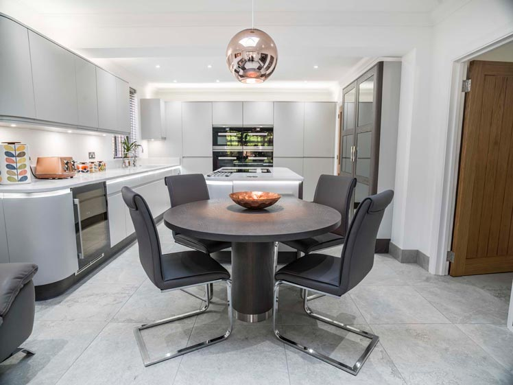 Light grey kitchen with copper pendant light over dining table