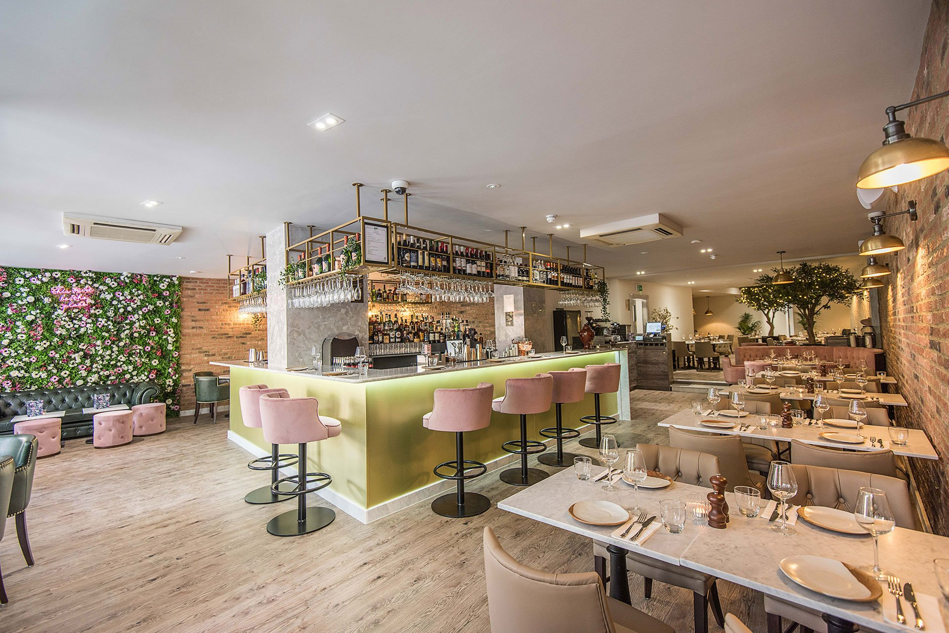 Interior of Booca Social restaurant with wooden dining tables and central lime green bar with pink bar stools