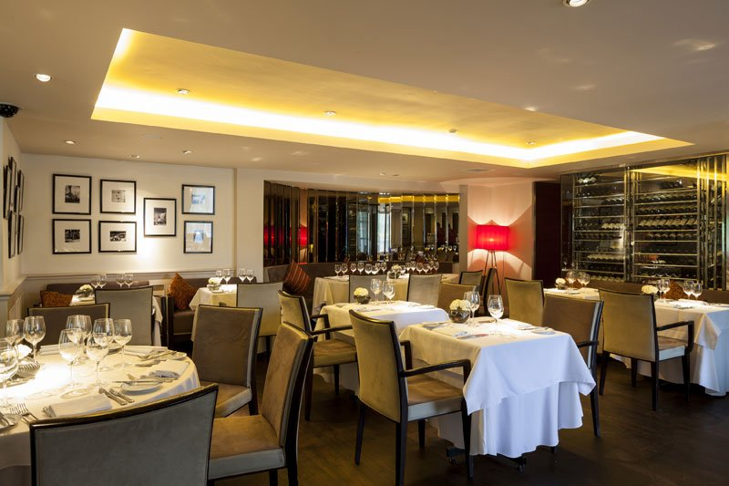 Interior of Chapter One restaurant, formal dining with white tablecloths and monochrome colour scheme