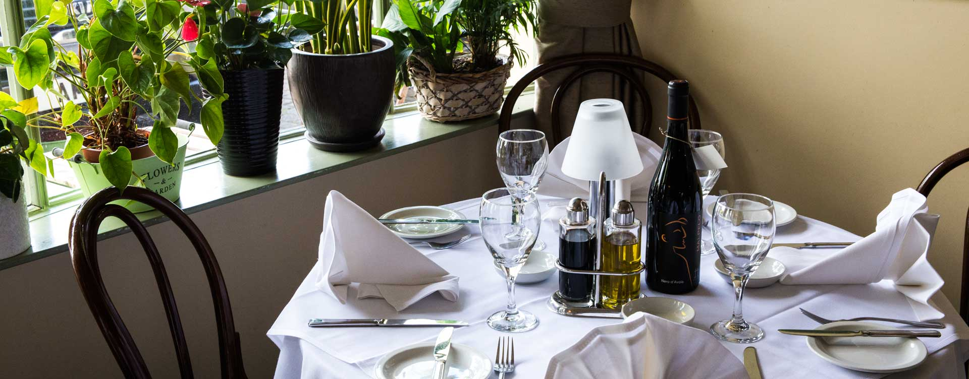 Close up on formally set restaurant table at Due Amici with plants on windowsill