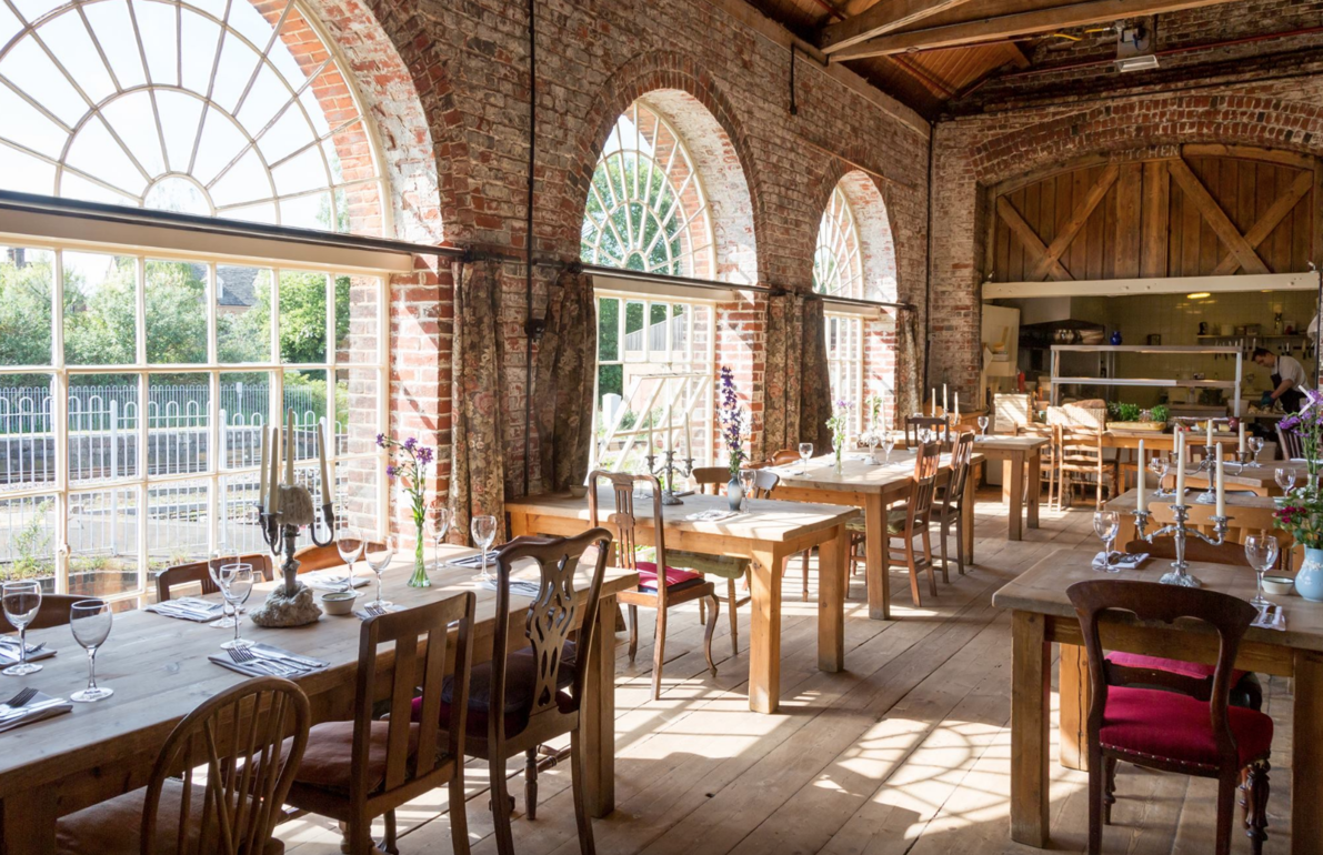 Large VIctorian windows make a light dining area for the rustic wooden interiors at The Goods Shed