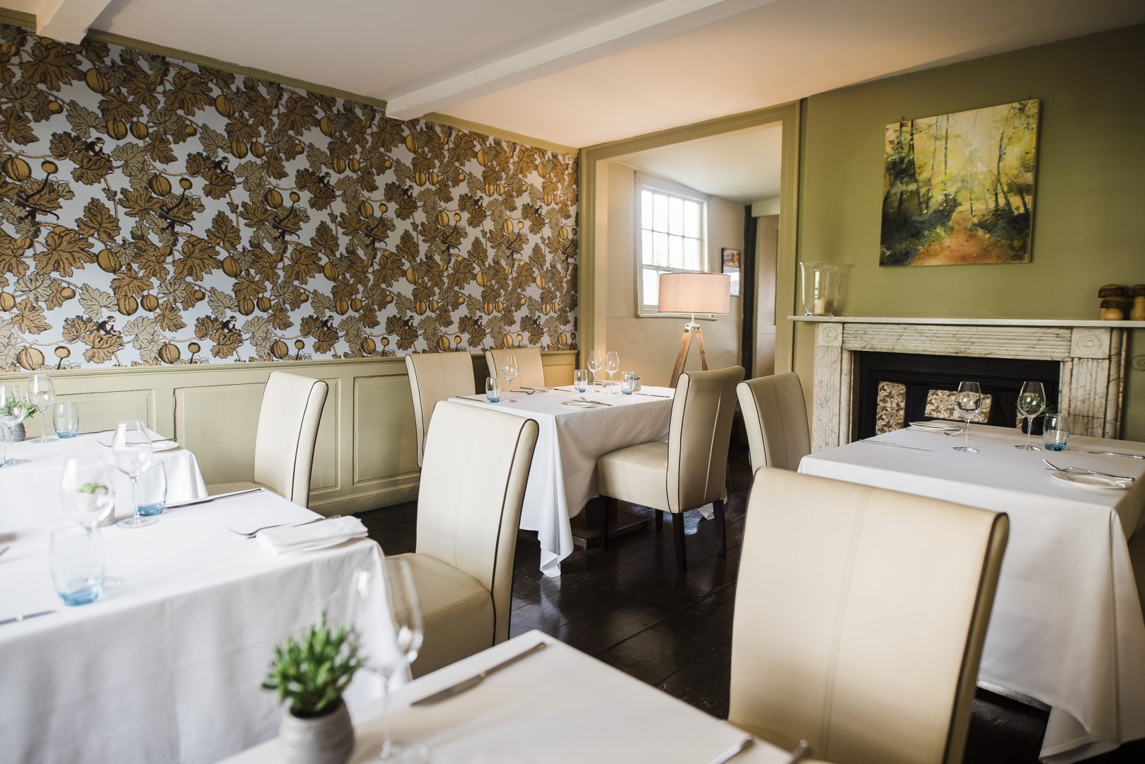 Dining room at Thackerays' restaurant with patterned wallpaper and historic fireplace features