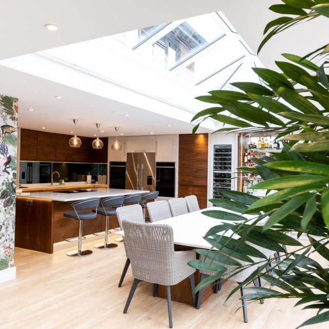 walnut kitchen with nature wallpaper, plants and dining table