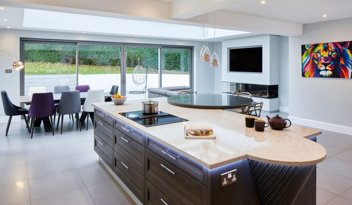Dark oak kitchen island with bi-fold doors with view of the garden