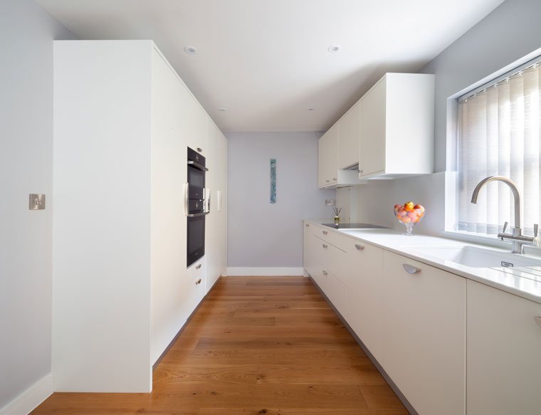 white galley kitchen with floor to ceiling cupboards